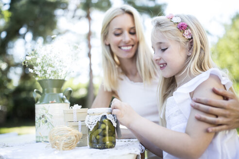 Smiling mother and daughter with preserved gherkins outdoors - WESTF22821