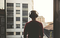 Man wearing headphones on a balcony in the city at sunset - EPF00390
