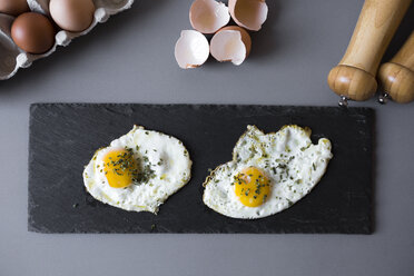 Eggs sunny side up with herbs on a slatte - GIOF02142