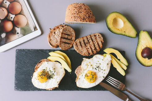 Breakfast with eggs, avovados and toasted bread on a table with digital tablet - GIOF02148