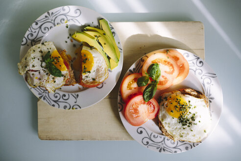 Delicious eggs with tomatoes and avocado on the table - GIOF02166