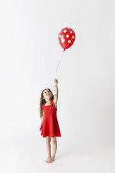 Smiling little girl in a red dress  holding polka dot red balloon looking up in front of white background - LITF00511