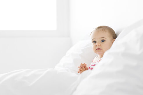 Portrait of baby girl sitting on a white bed between pillows - LITF00523