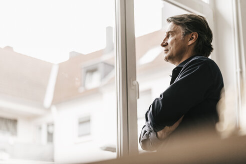 Mature businessman looking out of window - JOSF00694
