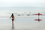 Woman carrying surfboard at the sea - KNTF00675