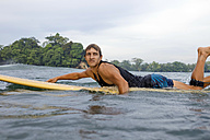 Indonesia, Java, man lying on surfboard on the sea - KNTF00681