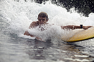Indonesia, Java, water splashing over man surfing - KNTF00699