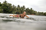 Indonesia, Java, smiling woman lying on surfboard on the sea - KNTF00705