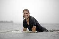 Indonesia, Java, smiling man on surfboard on the sea - KNTF00720