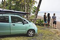 Indonesia, Java, friends standing at the coast next to car with surfboards - KNTF00726