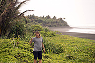 Indonesia, Java, man using cell phone at the coast - KNTF00729