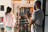 Young couple standing on balcony,taking smart phone pictures - VABF01259