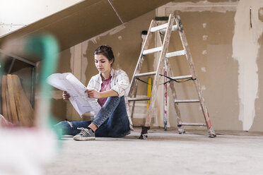 Young woman renovating her new home, holding construction plan - UUF10082