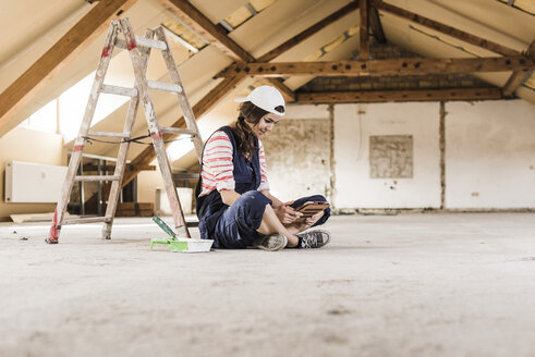 Young woman sitting on construction site, looking on her digital tablet - UUF10091