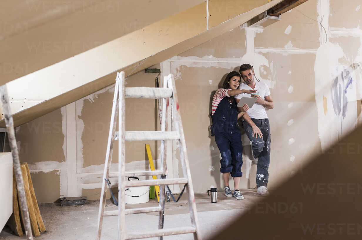 Young couple on construction site of their new home, using digital tablet - UUF10109 - Uwe Umstätter/Westend61