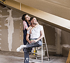 Young couple on construction site of their new home - UUF10112