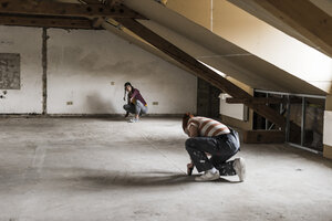 Young man and woman measuring floor on construction site - UUF10124