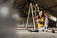 Independent young woman renovating her new home, sittiing on floor with cup of coffee - UUF10139
