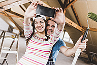 Young couple renovating their new home, taking smart phone selfies - UUF10142