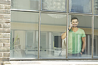 Young professional at the window talking on the phone, looking confident - SBOF00301