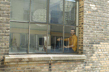 Young professional sitting at the window, looking confident - SBOF00304