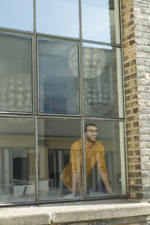 Young professional standing at the window, looking confident - SBOF00307