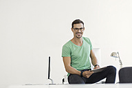 Young businessman in office sitting on desk with digital tablet - SBOF00316