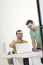 Two businessmen working together in office, using laptop - SBOF00319