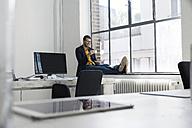 Businessman sitting on window sill, drinking coffee - SBOF00328