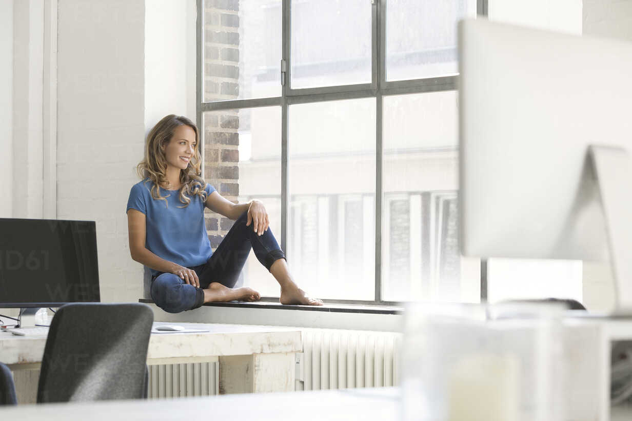 Casual businesswoman in office, sitting on window sill - SBOF00334 - Steve Brookland/Westend61
