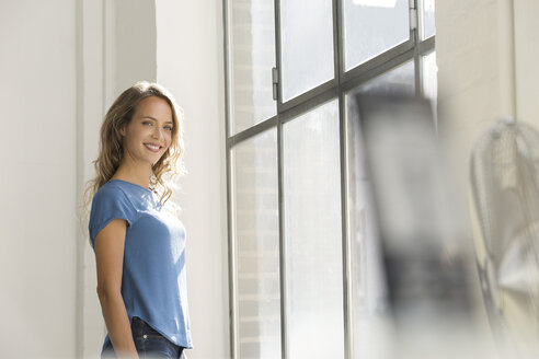 Casual businesswoman in office looking out of window - SBOF00337
