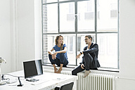 Colleagues sitting on window sill, talking - SBOF00346