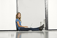Casual businesswoman in office sitting on floor, using laptop - SBOF00349