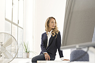 Businesswoman sitting on desk in her office - SBOF00358