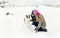 Two friends playing with a dog in the snow - MGOF03027