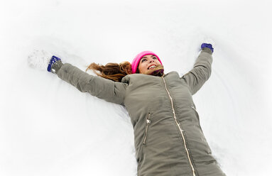 Young woman making a snow angel - MGOF03045