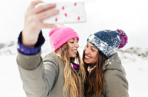 Two friends taking smart phone selfies in the snow - MGOF03057
