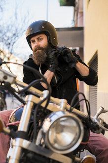 Portrait of bearded biker fastening helmet while sitting on his motorcycle - KKAF00491