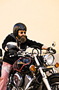 Portrait of bearded biker wearing helmet and sunglasses sitting on his motorcycle - KKAF00494