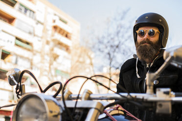 Portrait of bearded biker wearing helmet and sunglasses sitting on his motorcycle - KKAF00497