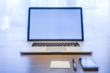 Smartphone, ballpen, adhesive note and laptop on desk - TCF05313