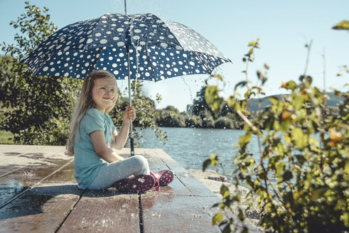 Girl with umbrella sitting on a jetty at  lake while waterdrops falling down on her - IPF00366