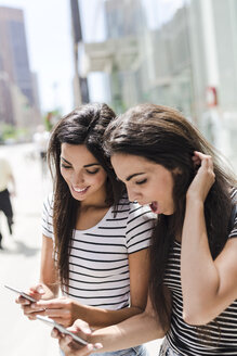 USA, New York City, two happy twin sisters looking at cell phones in Manhattan - GIOF02179