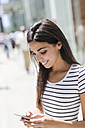 Smiling young woman looking at cell phone in the city - GIOF02182