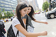 USA, New York City, two happy twin sisters on the go in Manhattan - GIOF02194