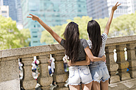USA, New York City, back view of two young women in Manhattan having fun - GIOF02209