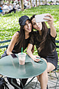 Two twin sisters taking a selfie at table in a park - GIOF02212