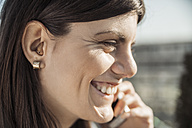 Happy young woman with hearing aid on the phone - ZEDF00553