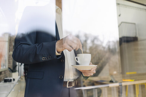 Businessman with cup of coffee at the window - KNSF01159