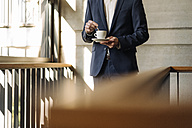 Businessman with cup of coffee in staircase - KNSF01165